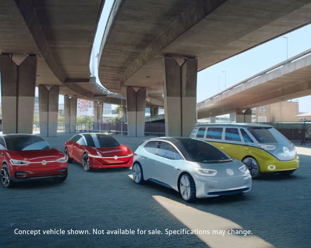 Four VW electric concept vehicles parked under a highway overpass