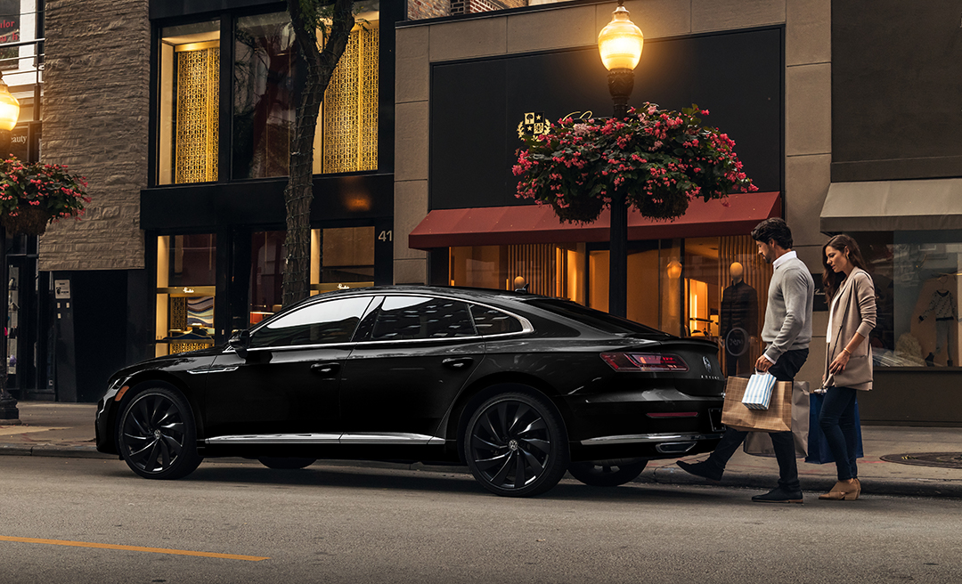 Man and woman at rear of Arteon in Deep Black Pearl