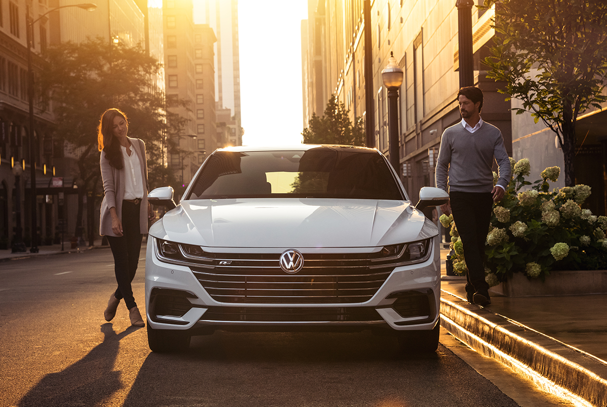 Couple standing on either side of a Pure White Arteon