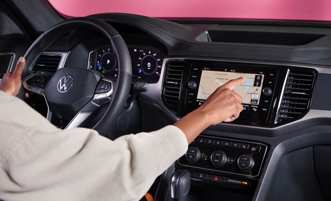 A woman taps the screen of the available navigation system featured in the Atlas Cross Sport.