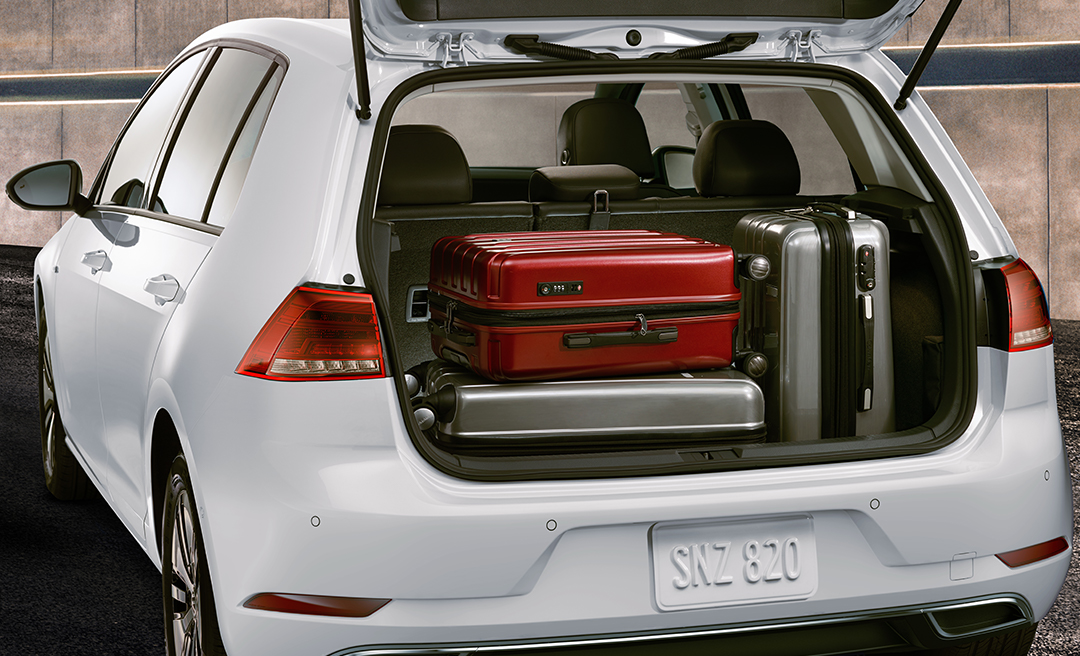 Open hatchback reveals cargo space with three suitcases neatly packed in
