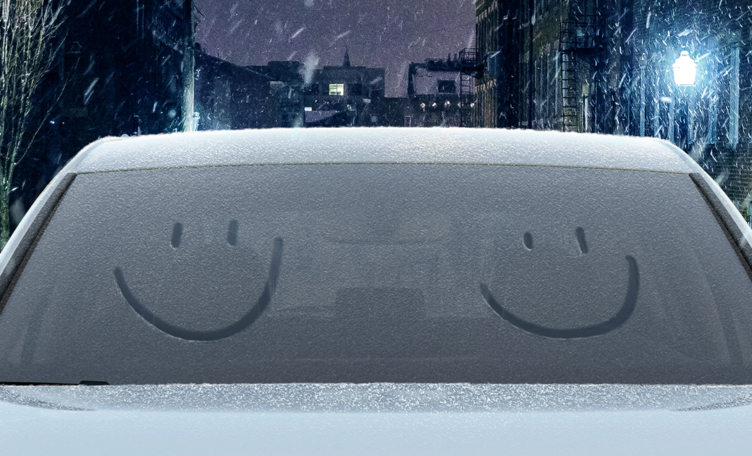 Snow-dusted windshield with two smiley faces drawn in