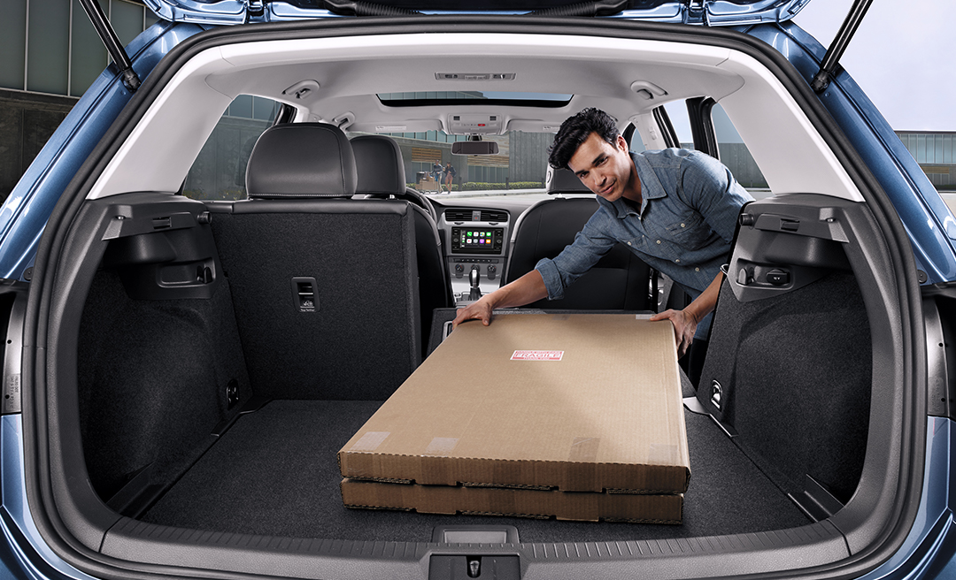 Man loading cargo into the trunk from second row