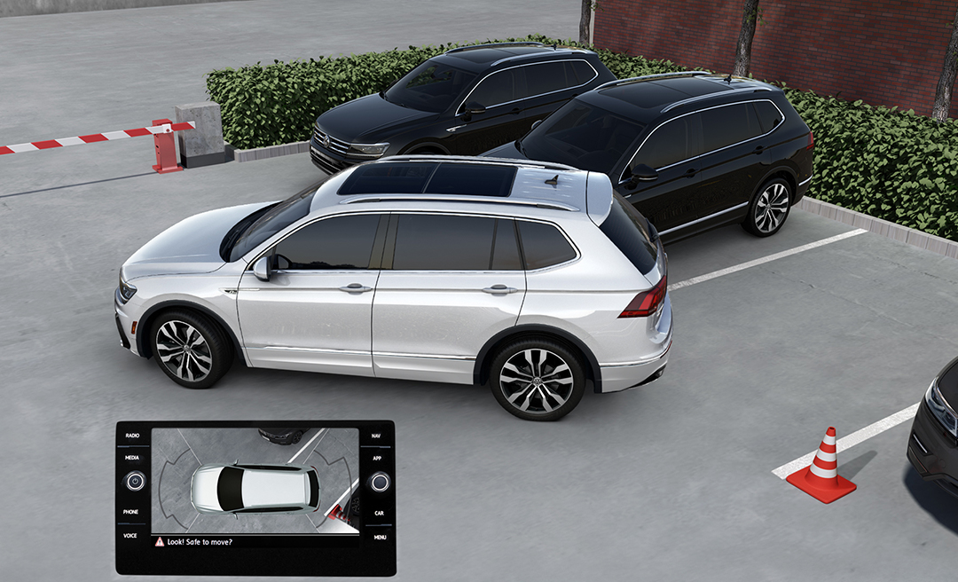 Pure White Tiguan parking next to Deep Black Pearl Tiguan with a snapshot of the available Overhead View Camera's Area View in the lower left corner