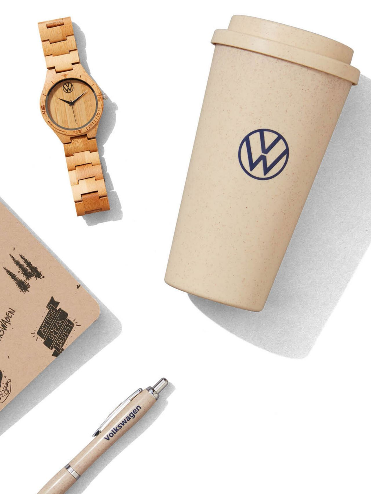 A collection of four VW Driver Gear products including a tumbler, pen, notebook, and watch.